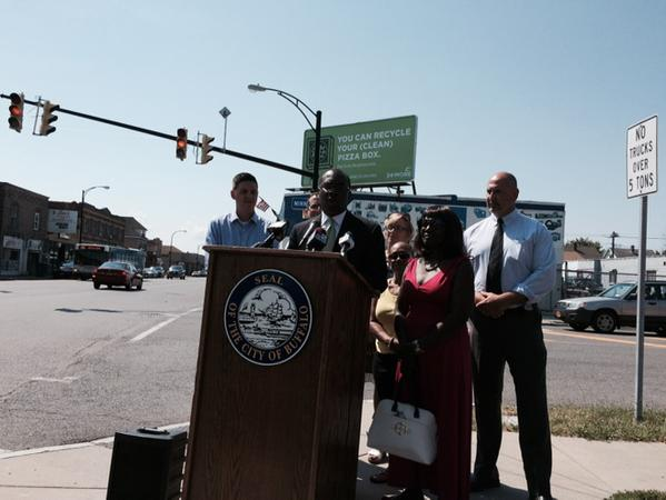 A billboard behind city officials says residents can recycle clean pizza boxes.