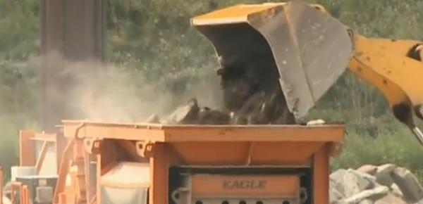 A tractor dumps debris onto Battaglia's crusher (Photo: WGRZ)